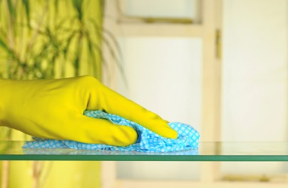 Person's hand cleaning a table